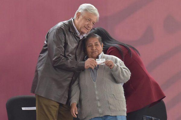 idoso-recebe-cartao-de-aposentado-das-maos-de-obrador-foto-eduardo-miranda-proceso-1-600x400